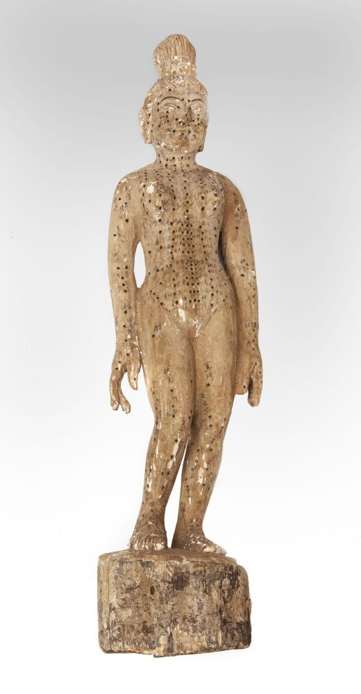 """An """"annotated"""" female acupuncture model, with pressure-point holes all over the body & characters for each point written in black, 835 x ca. 190 mm., five kilos (11 lbs.), sculpture carved from wood. ACUPUNCTURE STUDY MODEL."""