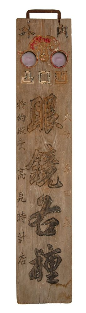 """Wooden double-sided kanban (shop signboard) for the """"Takami tokei ten,"""" an eyeglass & watch store, with """"Megane kakushu"""" (""""Variety of Eyeglasses"""") in the largest characters on the board. KANBAN: EYEGLASS, WATCH STORE'S SIGNBOARD."""