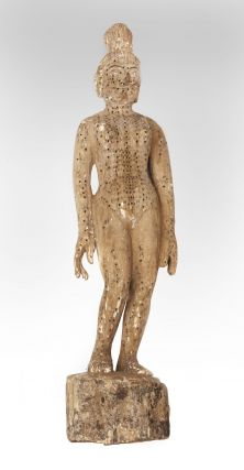 "An ""annotated"" female acupuncture model, with pressure-point holes all over the body..."